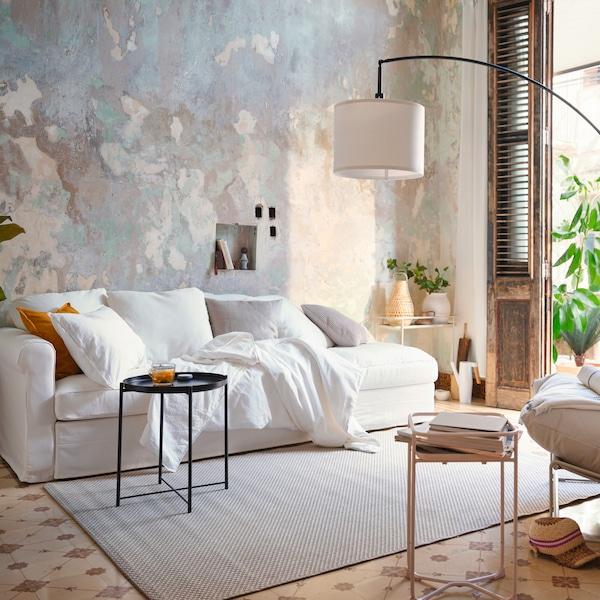 Fehér kanapé, bézs-szürke szobában, szétdobált díszpárnákkal, fekete kisasztallal és fehér fotellel.