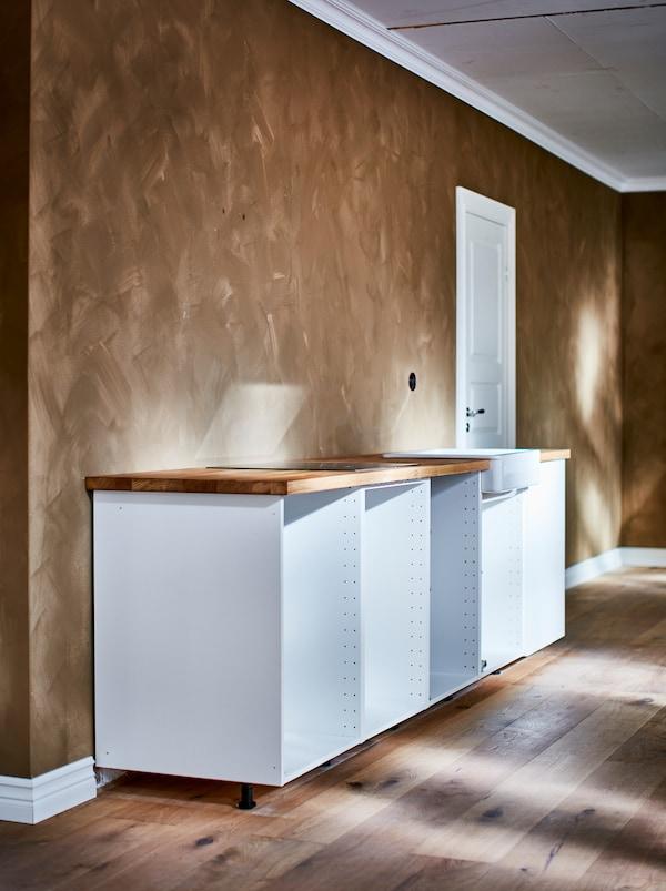 Fehér METOD alapszekrény váz, ajtók nélkül, a fal előtt, világosbarna árnyalatokkal, ecsetvonásos felülettel.