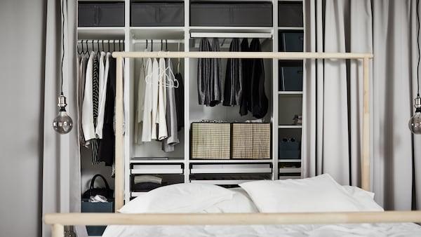Fehér PAX gardróbszekrény-kombináció különböző részein többféle ruhadarab, egy fehér paplannal letakart ágy mögött.