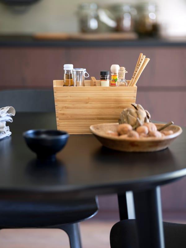 Fekete asztal és fekete-kék BALTSAR székek, az asztalon egy VARIERA bambusz dobozzal.