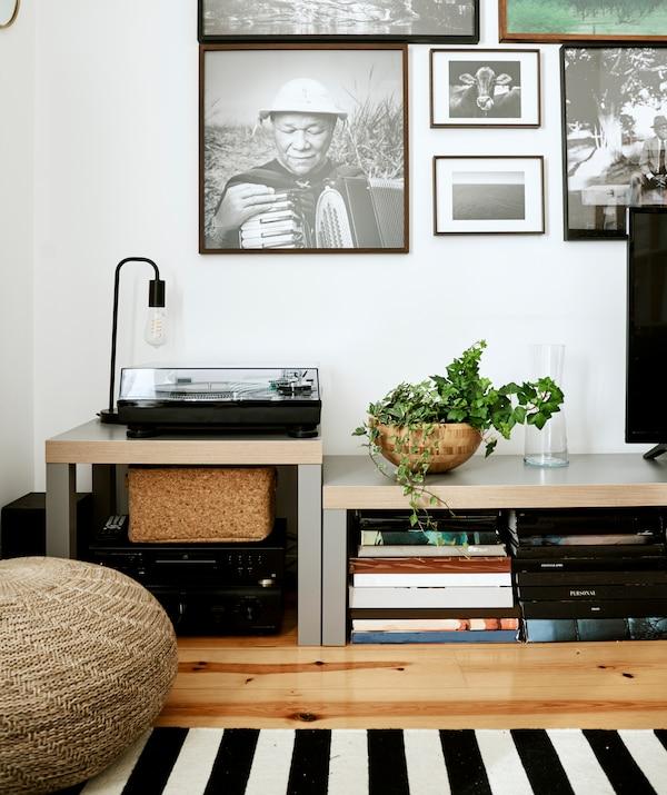 Fekete-fehér képek a falon két alacsony pad felett, az egyiken lemezjátszó, a másik alatt könyvhalom.