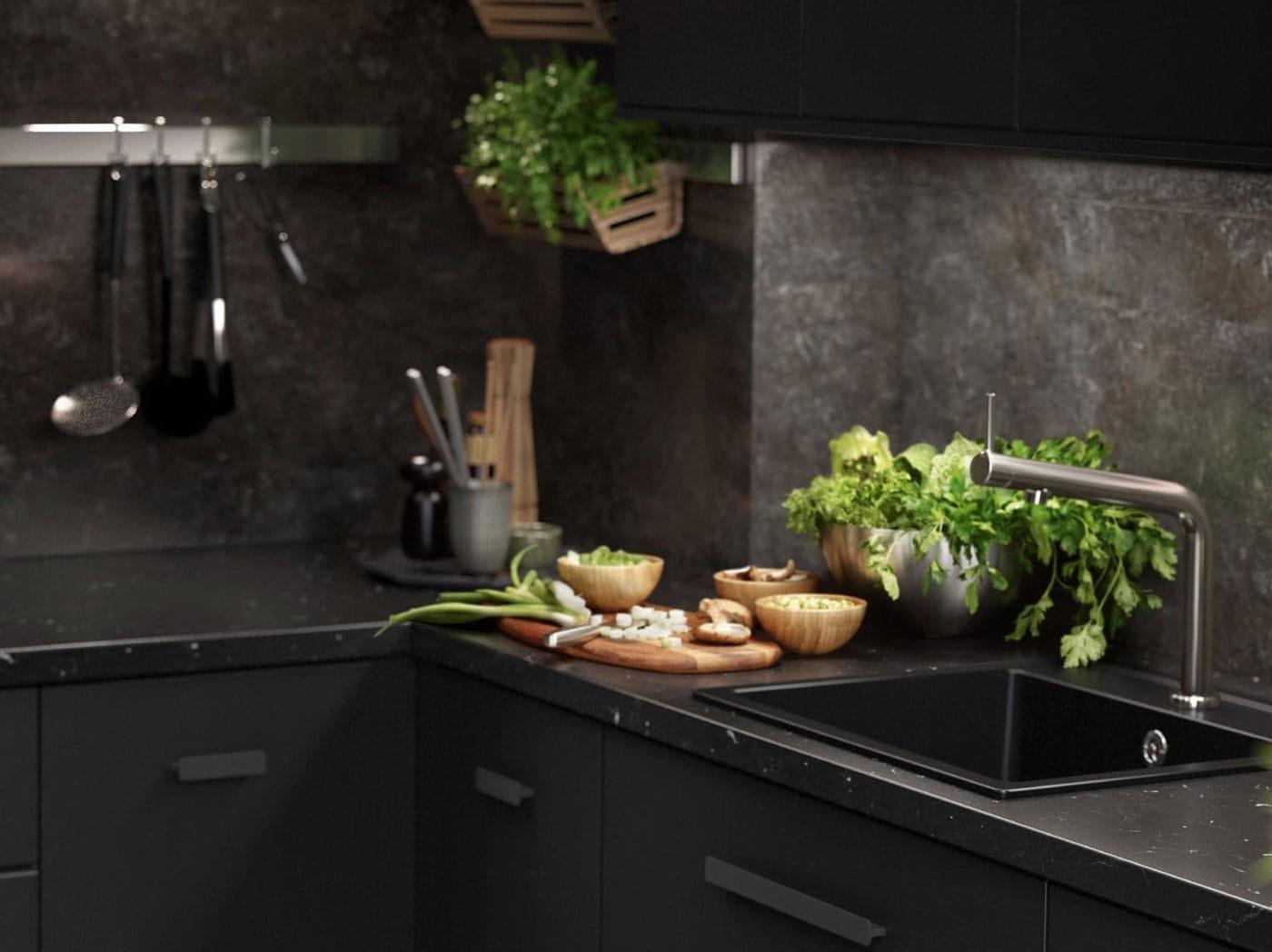 Fekete KUNGSBACKA konyha, márvány hatású jellemzőkkel, konyhai eszközökkel és friss fűszernövényekkel.