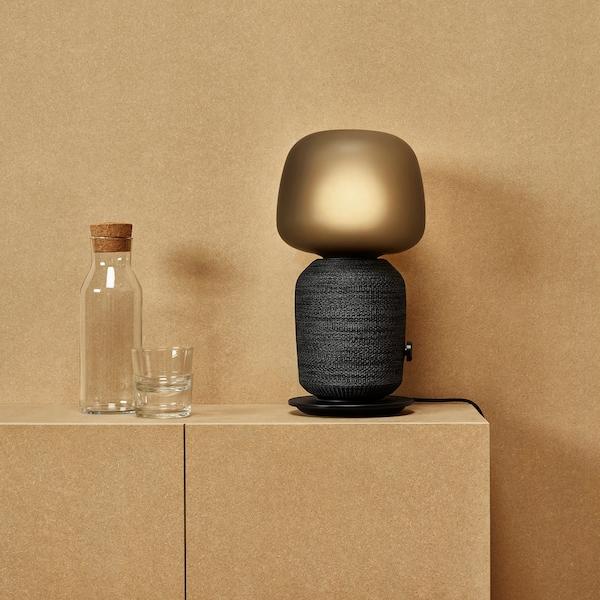Fekete SYMFONISK asztali lámpa, beépített WiFi hangfalakkal, egy pohár víz mellett, egy minimalista szobában.
