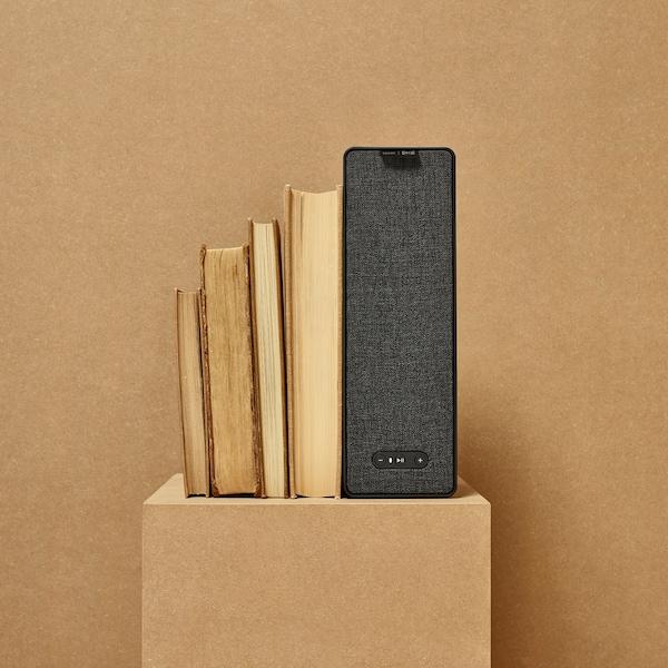 Fekete SYMFONISK WiFi könyvespolc hangfal egy polcon, könyvekkel.