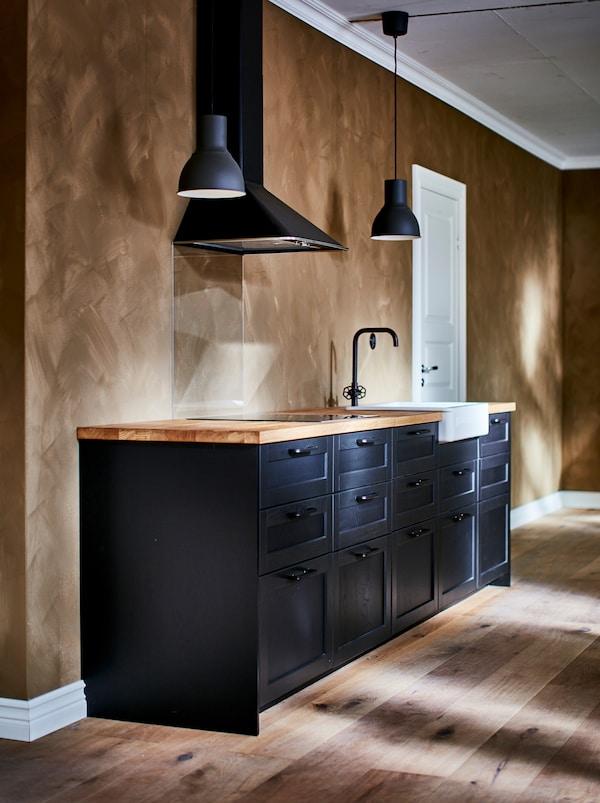 Feketére festett konyhabútor, fölötte sötétszürke HEKTAR függő lámpák, fekete csap és fehér, HAVSEN mosogatótál, melynek az eleje a konyhabútor frontja felől is látható.