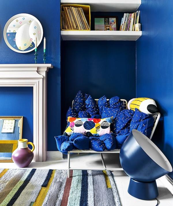 Felblauwe woonkamer met zitbank, oversized verlichting en vloerkleed