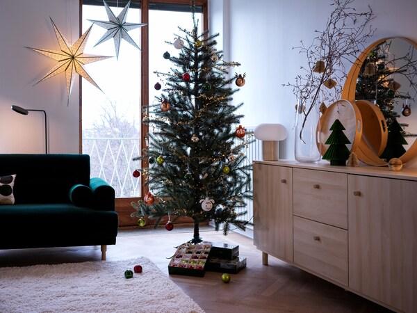 Feldíszített VINTER 2021 karácsonyfát látunk egy berendezett nappaliban, a fa alatt pedig egy doboz díszgömb hever.