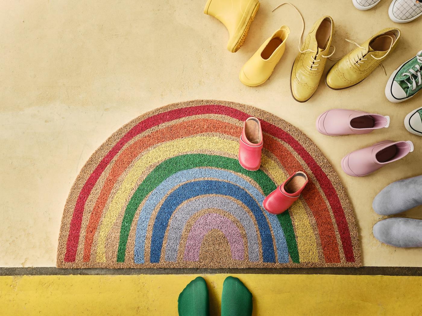 Felpudo PILLEMARK con diseño de arco iris sobre un suelo amarillo con zapatos de colores y un par de pies con calcetines verdes.