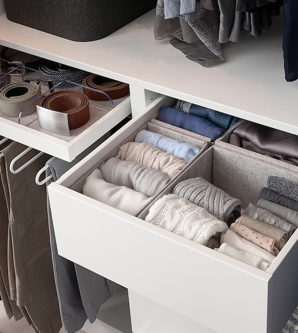 Felt KOMPLEMENT storage boxes in grey, filled with pastel coloured clothing, placed in a white drawer.