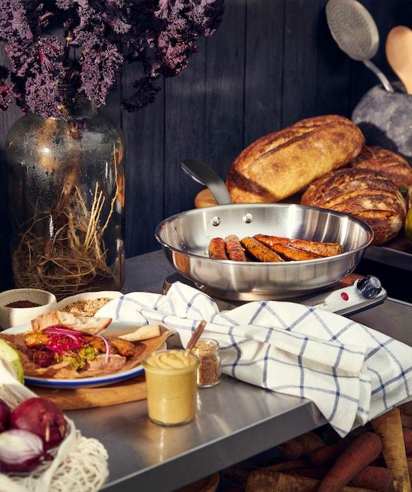Fém munkalap egy tányérral, rajta ételek, egy vekni kenyér és a konyhai mérlegen zöldséges rolók.