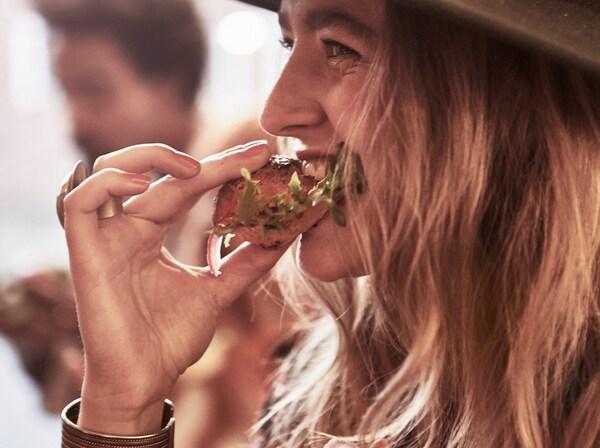 Femme à chapeau mordant dans un sandwich au saumon