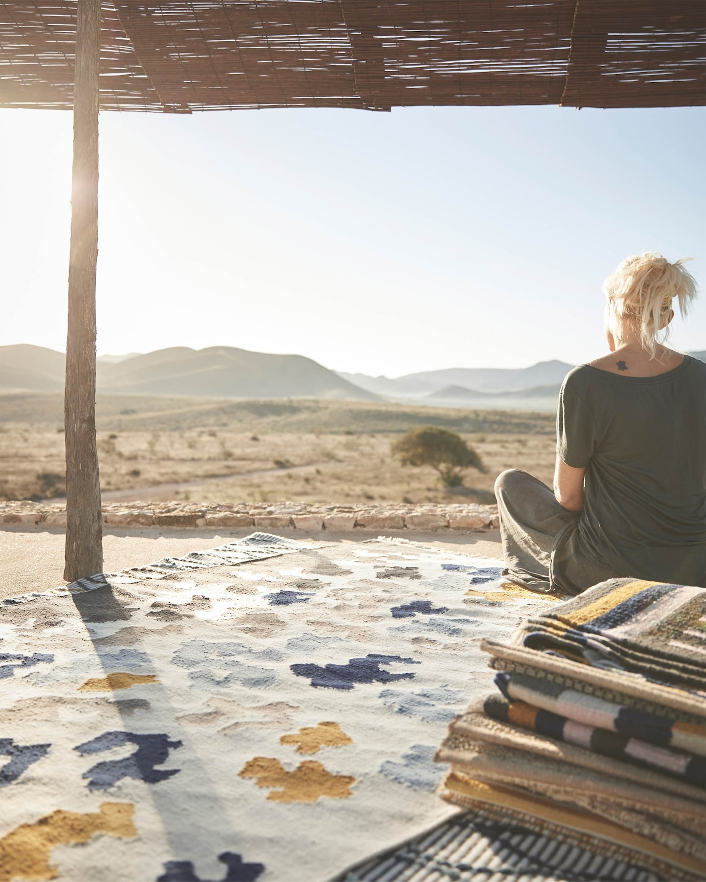 Femme assise à côté d'une pile de tapis sur un tapis 100% laine tissé à la main. Elle observe un paysage inondé de soleil.