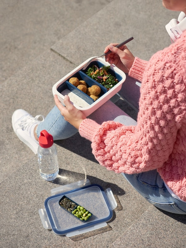 Femme assise à l'extérieur qui mange un repas dans une boîte-repas IKEA 365+ avec des séparations