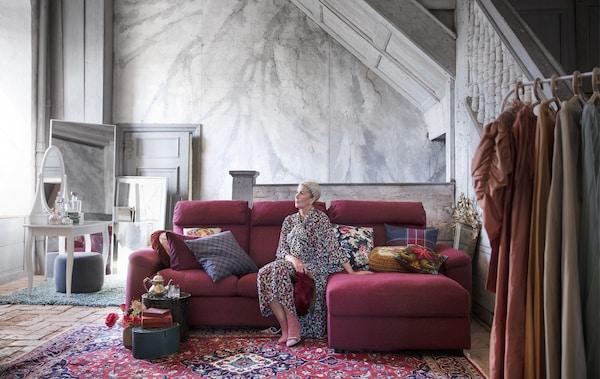 Femme assise sur un canapé modulaire dans une pièce aux murs revêtus de marbre.