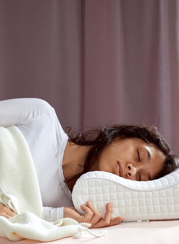 Femme aux cheveux bruns vêtue d'une chemise blanche, endormie sous une couverture blanche. Sa tête repose sur un oreiller ergonomique ROSENSKÄRM.