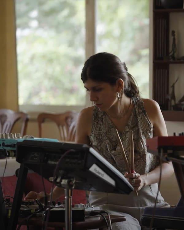 Femme blanche aux cheveux bruns assise devant un écran, des baguettes en main.