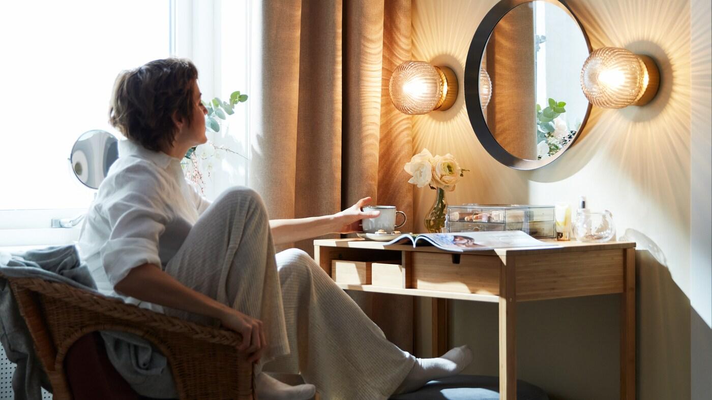 Femme dans un fauteuil, instant détente, elle prend sa tasse posée sur sa coiffeuse. Sur la coiffeuse, il y a également un magazine, un vase avec des fleurs et une boîte transparente.