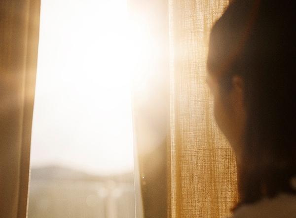 Femme de dos ouvrant des rideaux et regardant le soleil par la fenêtre