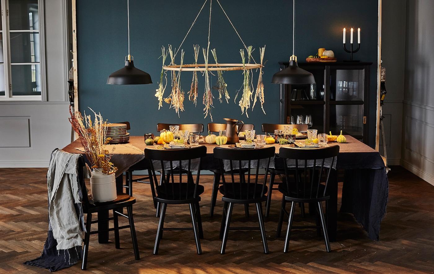 Femme en train de poser des assiettes sur une table décorée sur le thème des bienfaits de l'automne.