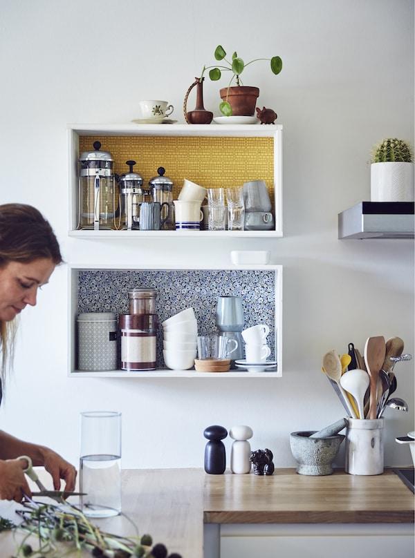 Femme en train de sectionner des tiges de plantes dans une cuisine.