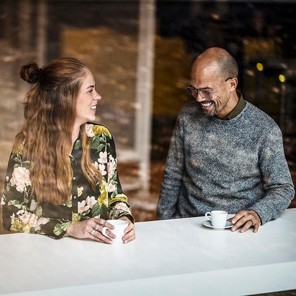 Femme et homme assis à une table, une tasse dans leurs mains