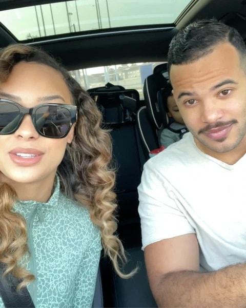 Femme et homme dans une voiture, enfant dans un siège auto à l'arrière-plan.