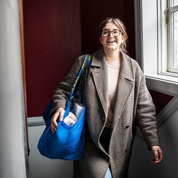 Femme portant un sac bleu IKEA à l'épaule