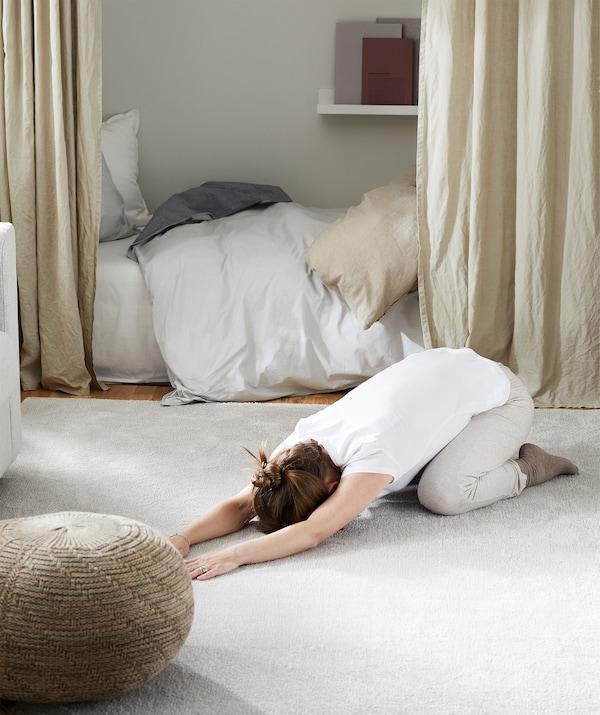 Femme qui fait de l'exercice sur un tapis de salon, ayant écarté les meubles.