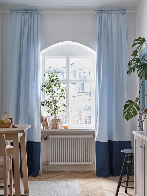 Fenêtre de cuisine arrondie avec grosse plante sur le bord et rideaux opaques bleu pâle BENGTA de chaque côté.