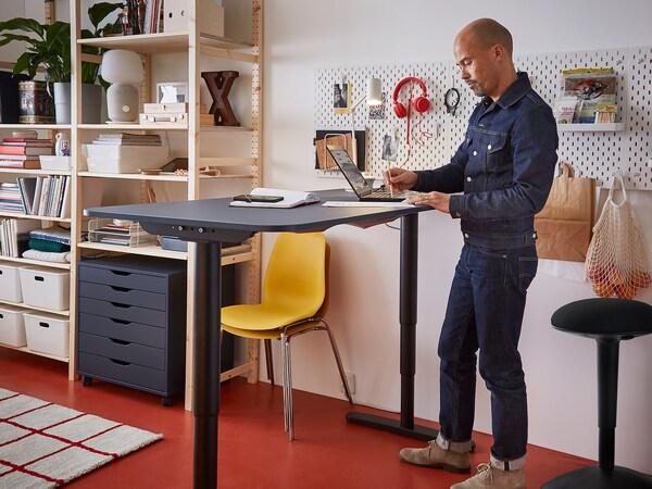 Férfi állva dolgozik egy magas asztalnál.