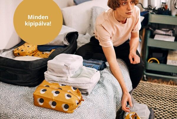 Fiatal fiű egy ágyon ülve csomagolja a holmiját.