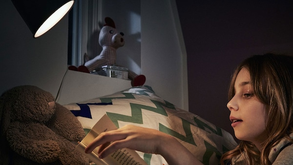 Fiatal lány fekszik az ágyban, és könyvet olvas egy lámpa alatt.