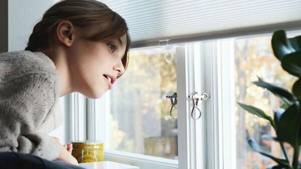 Fiatal lány néz ki az ablakon, az árnyékolók alatt.