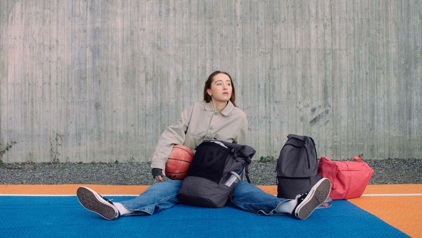 Fille tenant en main un ballon de basket, assise sur le sol d'un terrain basket avec à côté d'elle les sacs DRÖMSÄCK, VÄRLDENS et STARTTID.
