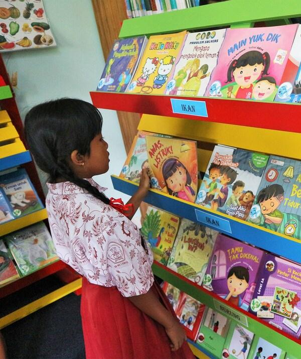 Fillette en train de choisir un livre dans une bibliothèque colorée.