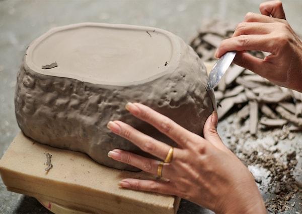Finition au couteau d'un bol irrégulier en céramique brun.