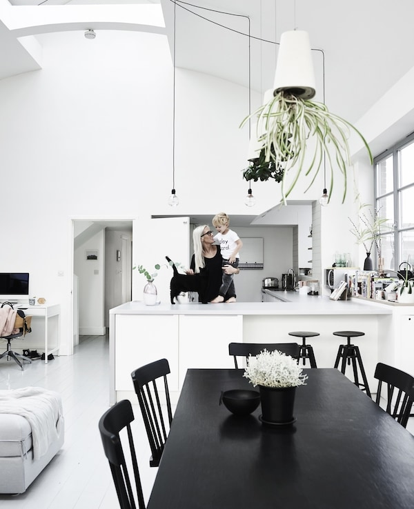 Fiona and her son, Stanley, in their all-white open plan kitchen area, including a vintage black dining table.