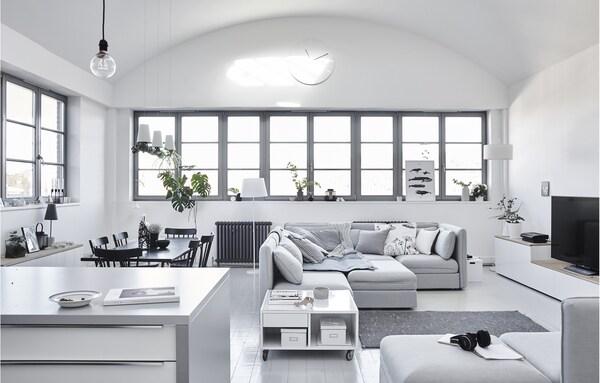 Fionaren egongela minimalista, eskandinaviar estilokoa, horma zuri, altzari zuri eta sofa argiekin.
