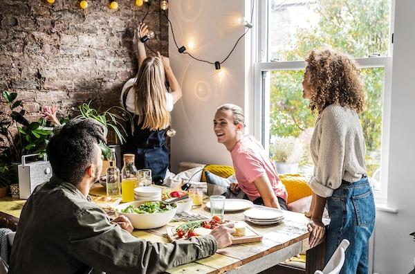 Fire venner sidder rundt om et bord der er dækket op.