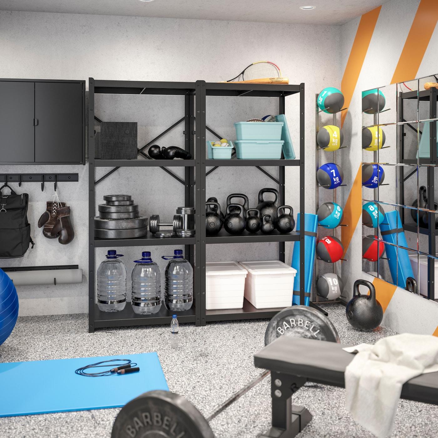 Fitnessraum mit schwarzem Regal, hellblauer Matte, Spiegel, schwarzen Hanteln & Boxhandschuhen.