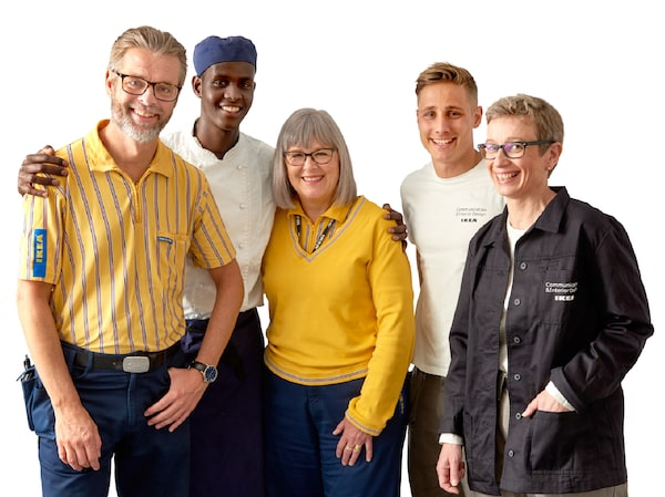 Five co-workers with a diversity of different uniforms standing against a white background.