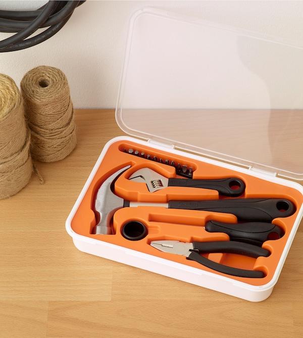 FIXA-työkalupakki, joka on täytetty erilaisilla työkaluilla, on asetettu puupinnalle.