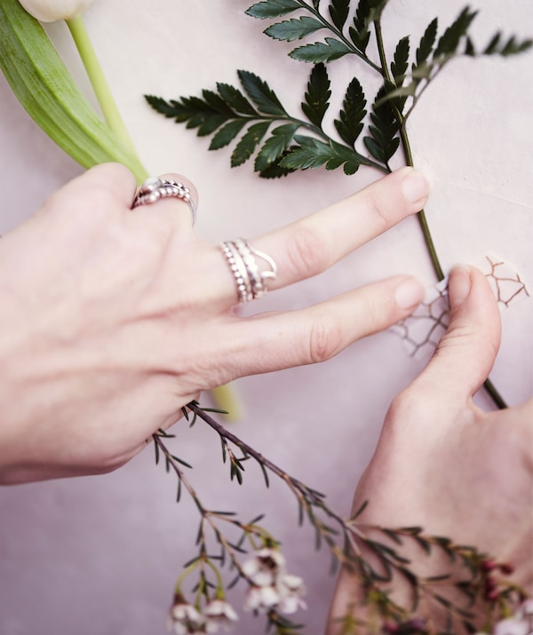 Fixing a flower stem to a white wall with monochrome patterned washi tape.