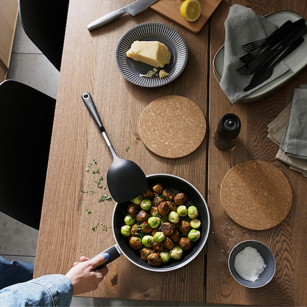 Flatlay of a wooden dinner table with cork trivets and a pan filled with veggie balls.