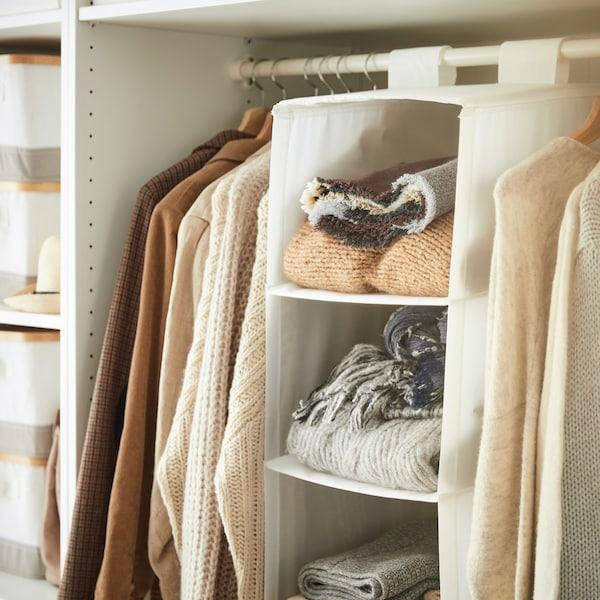 Fleksibel og hængende hvid opbevaring med seks rum (man kan se de tre øverste) i et hvidt garderobeskab.