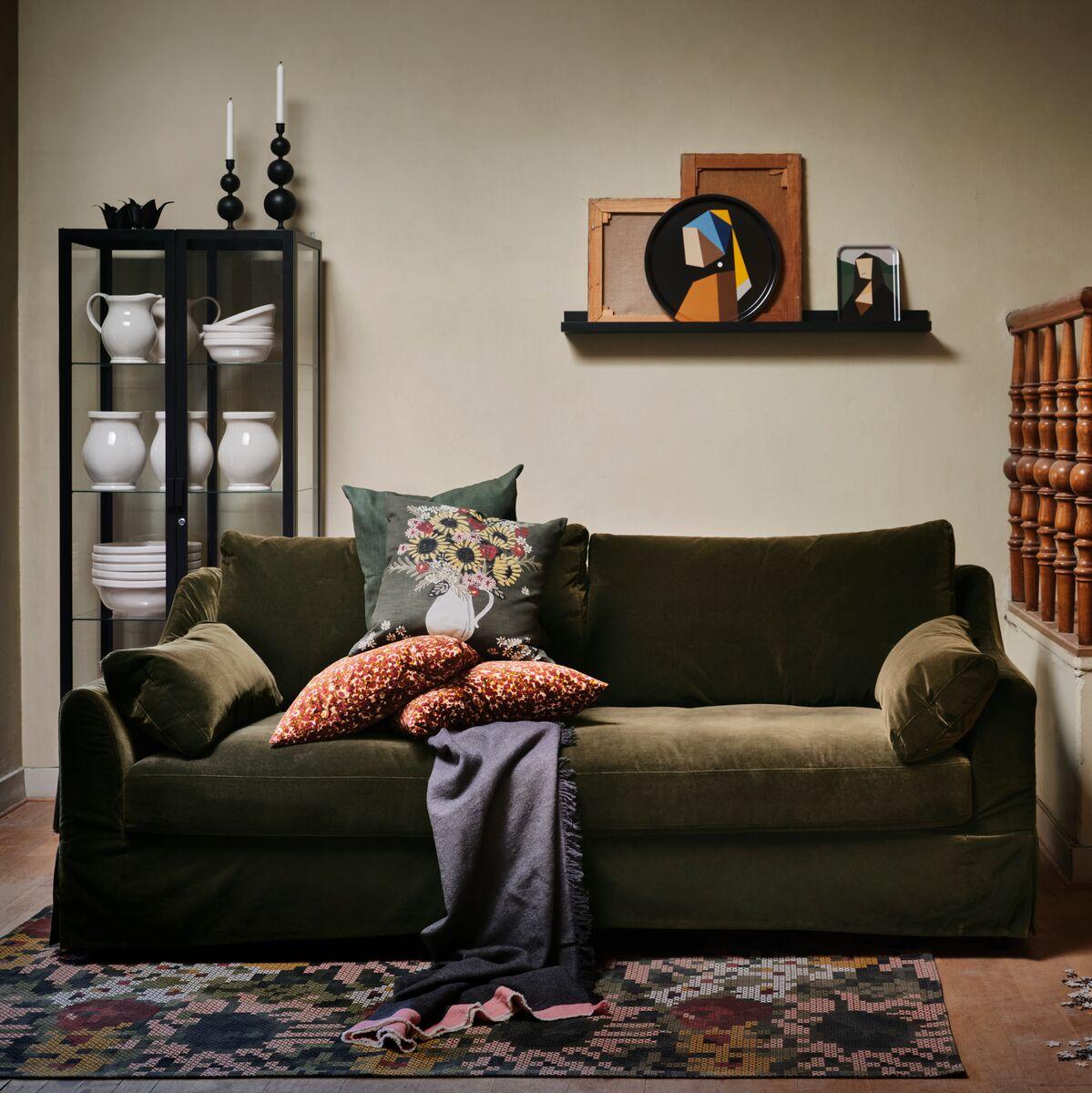 Flera föremål från IKEA DEKORERA kollektionen står i ett inbjudande vardagsrum med en mörkgrön soffa med kuddar.