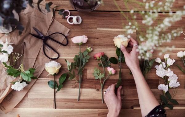 Fleurs artificielles et fleurs coupées variées, alignées sur une table en bois, à proximité de ciseaux et de rouleaux de ruban adhésif.