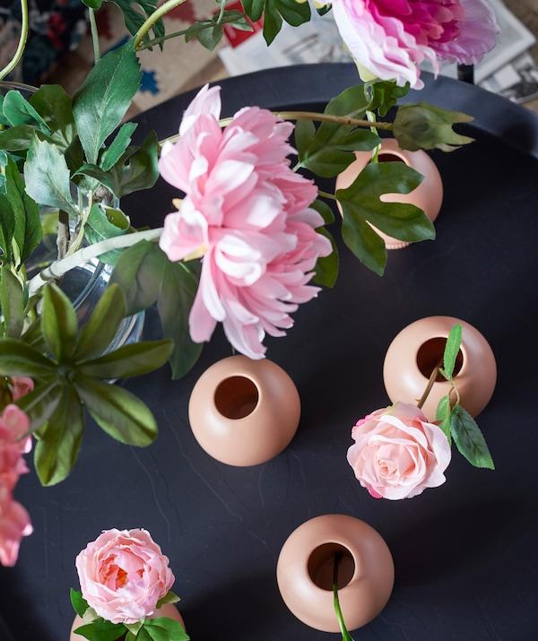 Fleurs roses artificielles dans des vases bruns, le tout posé sur une table noire.