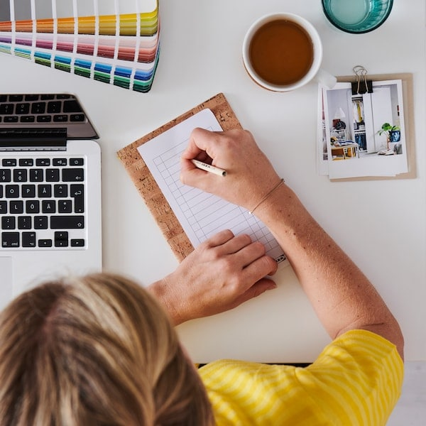Flicka i gul tröja och brunt hår sedd ovanifrån skriver på ett anteckningsblock och planerar.