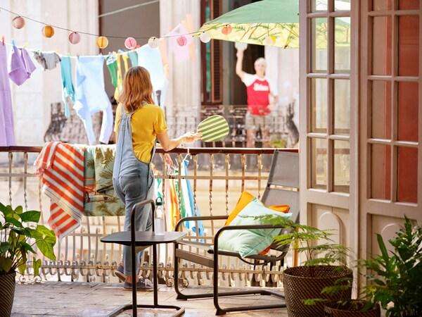 Flicka lutar sig mot ett balkongräcke och håller i ett strandtennisracket. Ljusslingor och en klädlina syns i bakgrunden.